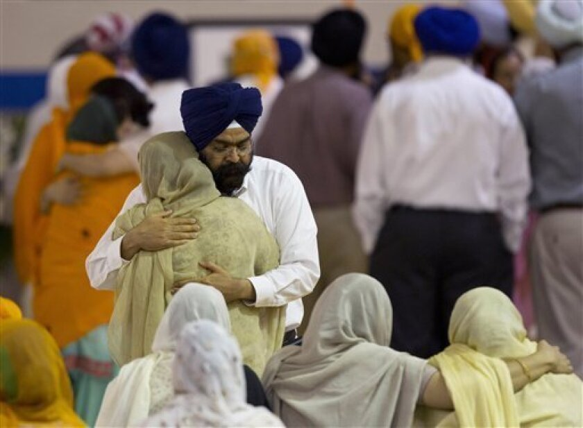 Mourners provide comfort Friday, Aug. 10, 2012 at the funeral and memorial service held in the Oak Creek High School for the six victims of Sunday's mass shooting at the Sikh Temple of Wisconsin in Oak Creek, Wis. Wade Michael Page, 40, killed five men and one woman, and injured two other men. Authorities say Page then ambushed the first police officer who responded, shooting him nine times and leaving him in critical condition. A second officer then shot Page in the stomach, and Page took his own life with a shot to the head. (AP Photo/Jeffrey Phelps)
