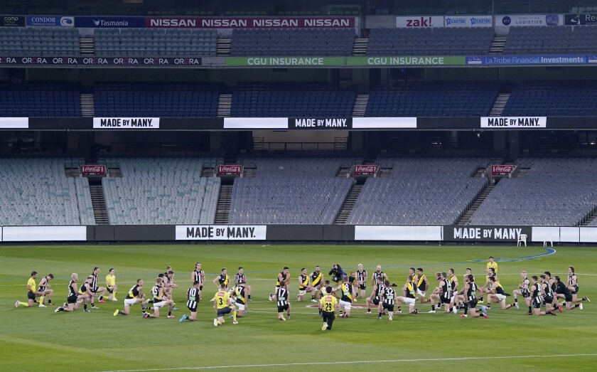 Australian Football League players from rivals Richmond and Collingwood teams, along with game officials, kneel before their game at the Melbourne Cricket Ground in Melbourne, Thursday, June 11, 2020, to show support for the Black Lives Matter movement. Aussie rules football is back after a three-month shutdown due to coronavirus restrictions. (Michael Dodge/AAP Image via AP)