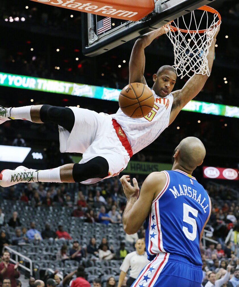 FILe - In this Dec. 16, 2015, file photo, Atlanta Hawks Al Horford hangs on the basket after dunking over 76ers Kendall Marshall during an NBA basketball game, in Atlanta. The Hawks All-Star said Wednesday, Feb. 17, 2016,  he expects to remain in Atlanta, and he is the ideal fit for coach Mike Bude