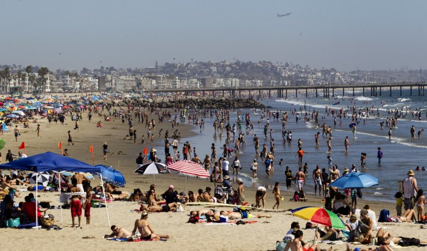 Beachgoers crowd Venice Beach, where a swimmer died Thursday after getting caught in a rip current.