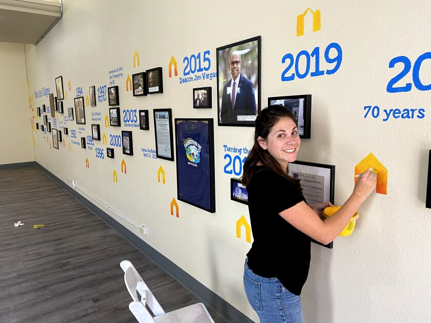 Ocean Beach resident Diane Lehman works on a history timeline mural she painted for Father Joe's Villages' 70th anniversary.