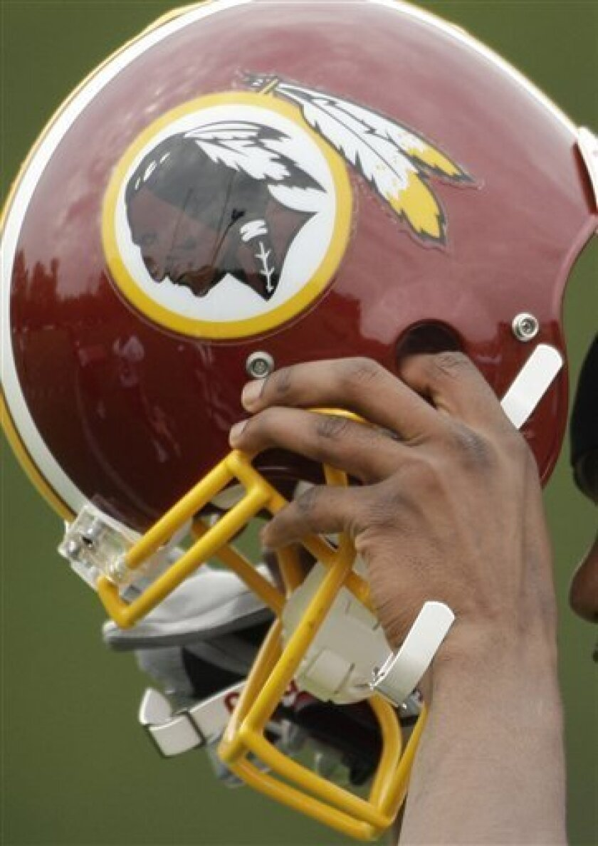 FILE - In t his May 1, 2009 file photo, Washington Redskins Marko Mitchell puts his helmet on during their NFL football minicamp practice at their training facility in Ashburn, Va. The Washington Redskins won another legal victory Friday, May 15, 2009, in a 17-year fight with a group of American Indians who argue the football team's trademark is racially offensive. The decision issued Friday by the U.S. Court of Appeals in Washington doesn't address the main question of racism at the center of the case. Instead, it upholds the lower court's decision in favor of the football team on a legal technicality. (AP Photo/Alex Brandon, File)