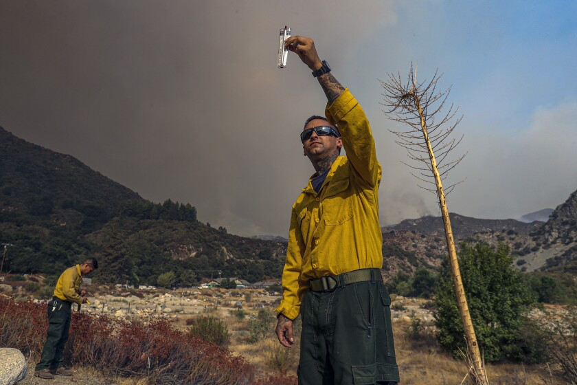 Angeles National Forest firefighters get weather readings as the Bobcat fire burns along Highway 39.