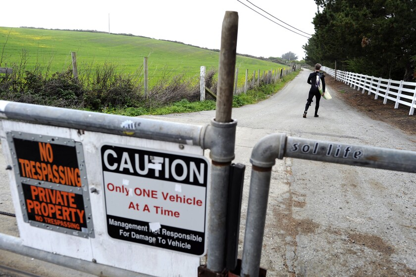 Surfer Mike Wallace of El Granada walks past a gate on his way to Martin's Beach in Half Moon Bay on March 12, 2013.