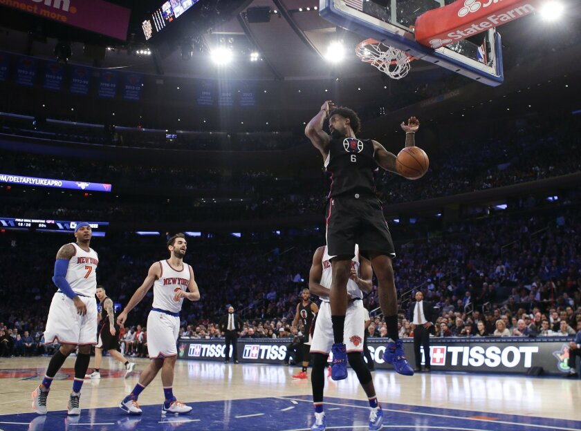 New York Knicks' Carmelo Anthony (7) and Jose Calderon (3) watch as Los Angeles Clippers' DeAndre Jordan (6) dunks during the first half of an NBA basketball game Friday, Jan. 22, 2016, in New York. (AP Photo/Frank Franklin II)
