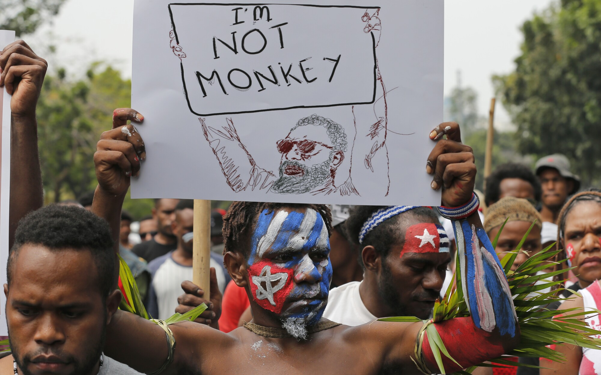 Papuan student, his face painted with the colors of the separatist Morning Star flag, holds a poster during a rally.