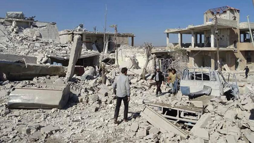 Syrians inspect damaged buildings after airstrikes in the village of Hass in the Idlib province on Wednesday.