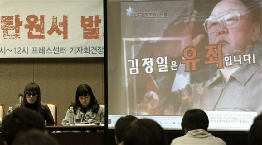 North Korean defector Kim Hae-young, left, and South Korean lawyer Lee Ji-hae participate in a press conference with a huge screen showing North Korean leader Kim Jong Il in Seoul, South Korea, Thursday, Dec. 3, 2009. A group of activists and North Korean defectors urged an international tribunal to investigate alleged human rights abuses in the North and put its authoritarian leader Kim Jong Il on trial. The group is to fly to The Hague next week to file its petition calling for an investigation at the International Criminal Court, the first such move on the North Korean rights issue, a lead activist said. (AP Photo/Ahn Young-joon)