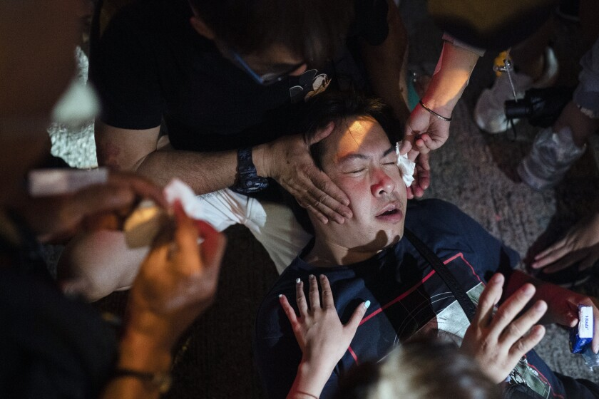 Volunteers help a man hit by police pepper spray near a protest Oct. 7 in Hong Kong.