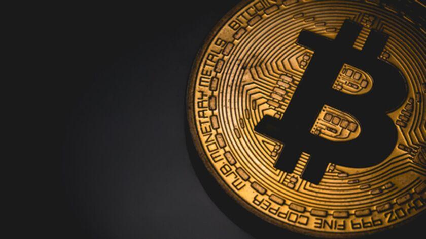 The bitcoin logo appears on a medallion.