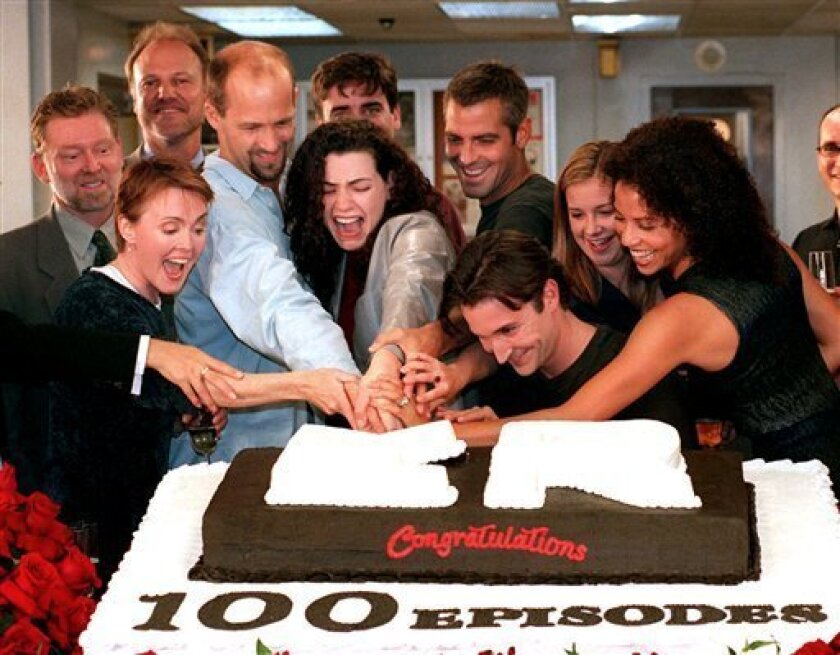 """In this Oct. 20, 1998 file photo, cast members, front row from left, Laura Innes, Anthony Edwards, Julianna Margulies, George Clooney, Noah Wyle, Kellie Martin, and Gloria Reuben, cut a cake celebrating the 100th episode of the NBC series, """"ER,"""" as NBC President Warren Littlefield, second row left, and series creator John Wells, look on. (AP Photo/Rene Macura, file)"""