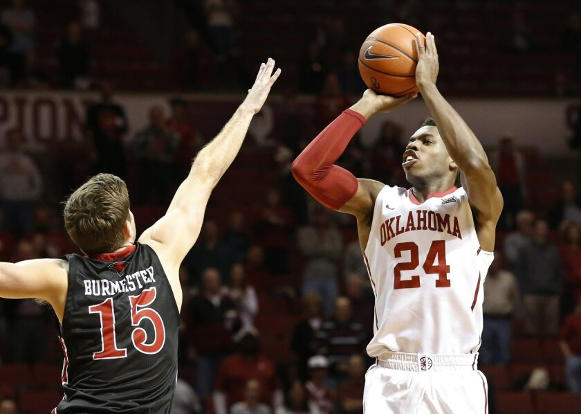 Oklahoma guard Buddy Hield (24) shoots as Incarnate Word guard Sam Burmeister (15) defends during the first half of an NCAA college basketball game in Norman, Okla., Tuesday, Nov. 24, 2015. (AP Photo/Sue Ogrocki)