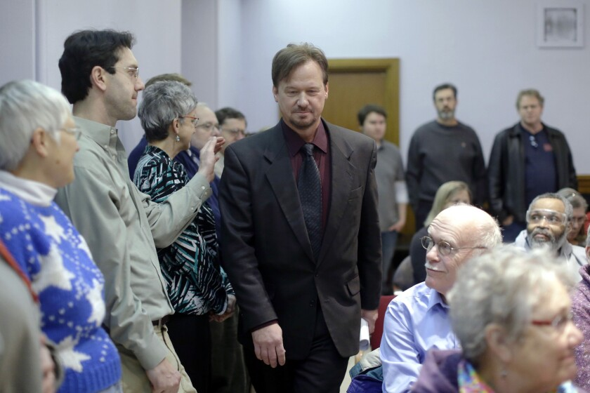 A man places a hand on the shoulder of the Rev. Frank Schaefer, a United Methodist clergyman suspended for officiating at his son's same-sex wedding, as he enters a news conference Monday at the Arch Street United Methodist Church in Philadelphia. Schaefer plans to defy a church order to surrender his credentials for performing a same-sex wedding.