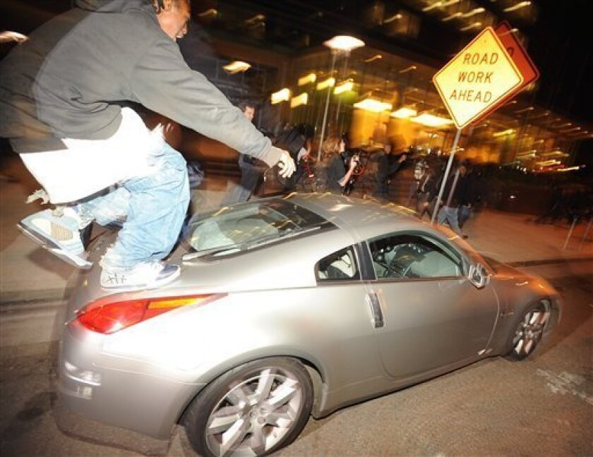 A man jumps on a car during rioting in Oakland on Wednesday, Jan. 14, 2009, shortly before breaking the vehicle's windshield. The violence, caused by a small group of people following a peaceful protest in support of shooting victim Oscar Grant, included dozens of car windows and more than 15 shatt
