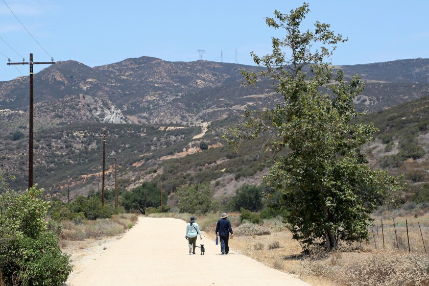 A couple walks their dog as they enter Black Star Canyon from the trailhead in Silverado.