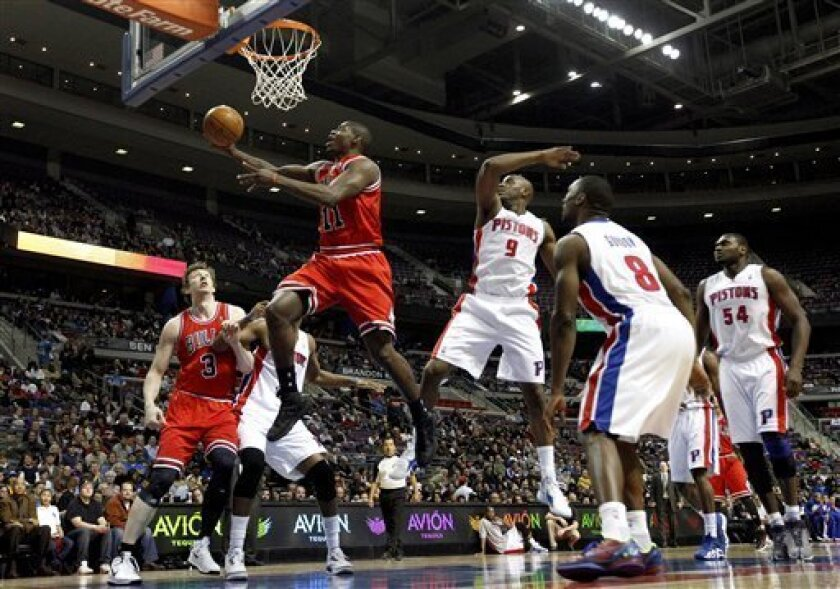 Chicago Bulls guard Ronnie Brewer (11) drives past Detroit Pistons' Damien Wilkins (9), Ben Gordon (8) and Jason Maxwiell (54) as Bulls' Omer Asik (3) looks on during the first quarter of their NBA basketball game in Auburn Hills, Mich., Wednesday, Jan. 4, 2012. (AP Photo/Paul Sancya)
