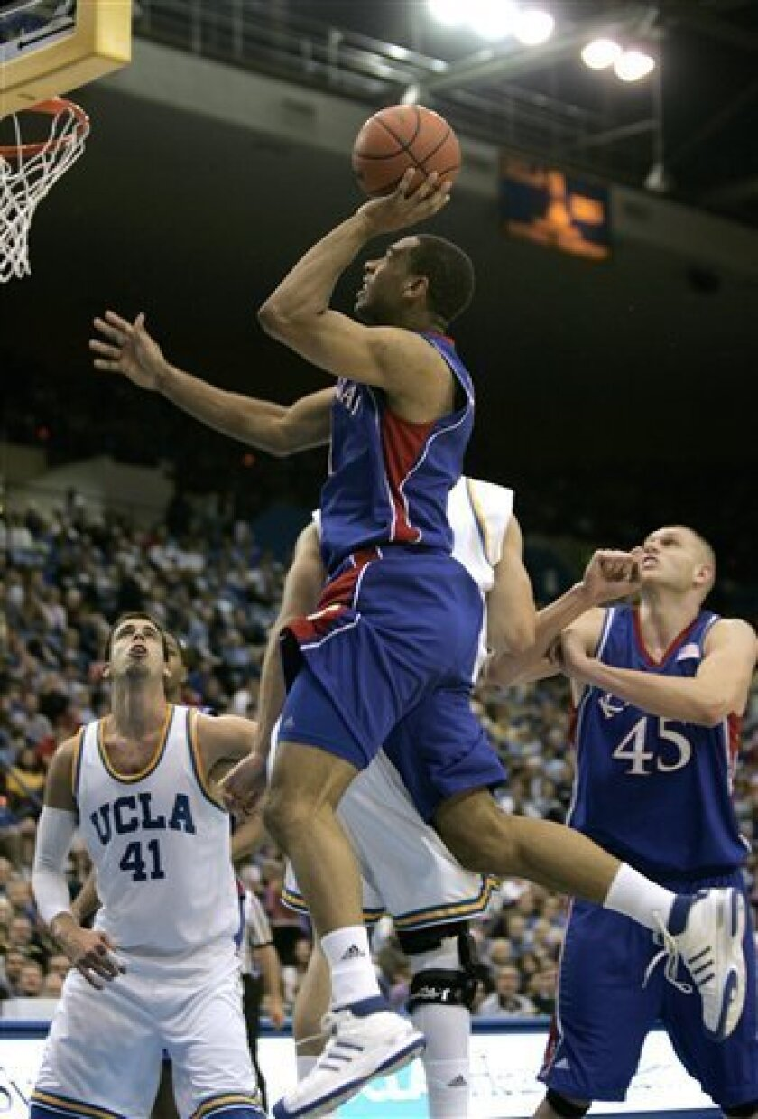 Kansas guard Xavier Henry, center, goes up for a shot as UCLA forward Nikola Dragovic (41) and Kansas center Cole Aldrich (45) look on in the first half of their NCAA college basketball game in Los Angeles on Sunday, Dec. 6, 2009. (AP Photo/Jason Redmond)