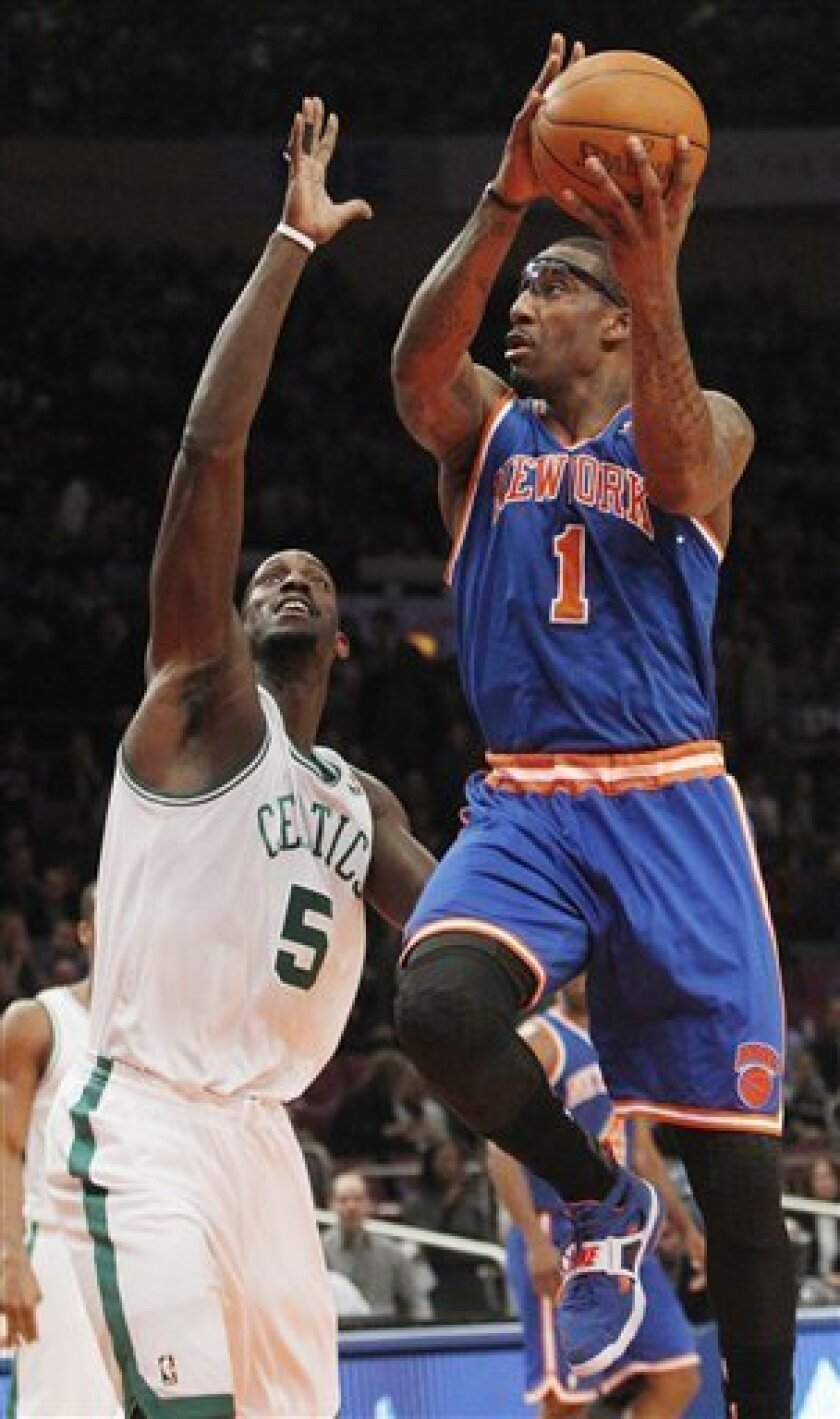 New York Knicks' Amare Stoudemire (1) drives past Boston Celtics' Kevin Garnett (5) during the first half of an NBA basketball game Monday, March 21, 2011, in New York. (AP Photo/Frank Franklin II)