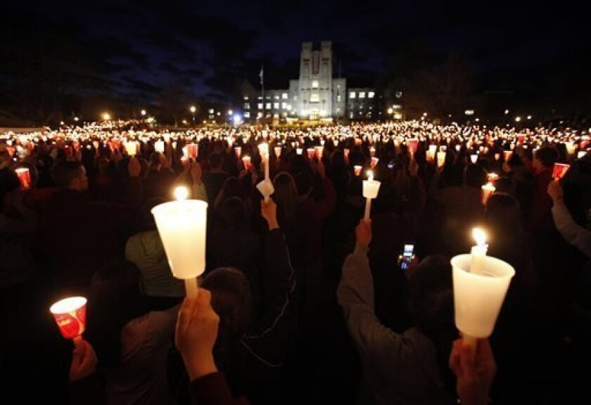 FILE - In this April 16, 2009, file photo, students, friends and family hold candles up during a candle light vigil marking the second anniversary of the April 16, 2007, shootings at Virginia Tech on the campus of the school in Blacksburg, Va. In recent years, America has had many scenes of mass sh