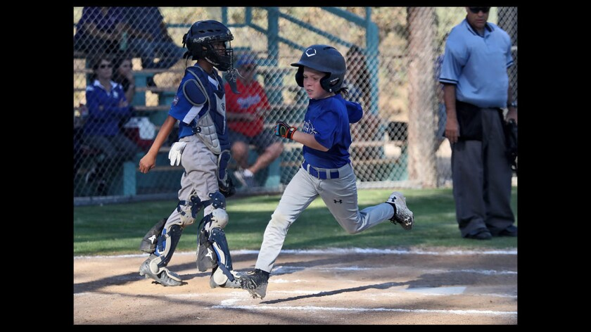 Crescenta Valley baseball player Aiden Lee scores after being walked in Minor Little League game vs. Burbank, at Tujunga Little League Fields in Tujunga, on Tuesday, June 5, 2018.