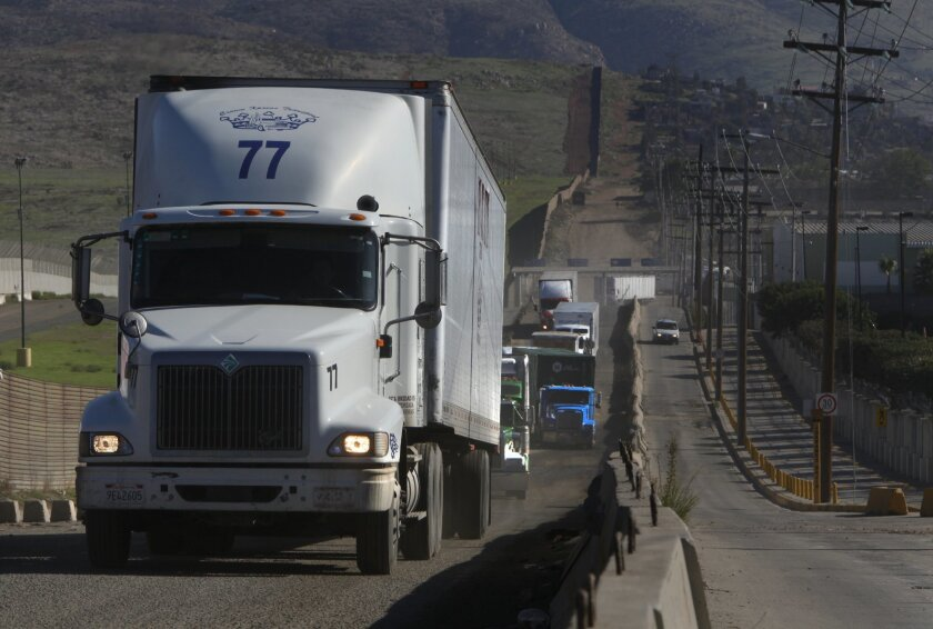 Trucks line the border fence in Otay Mesa on the Mexico side for the last mile before coming to the Port of Entry facility.
