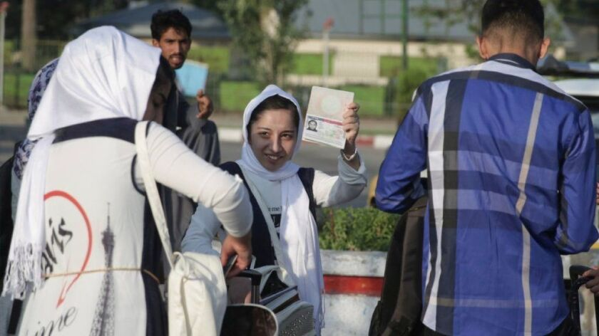 A member of a girls' robotics team from Afghanistan shows her U.S. visa as she leaves Kabul for the