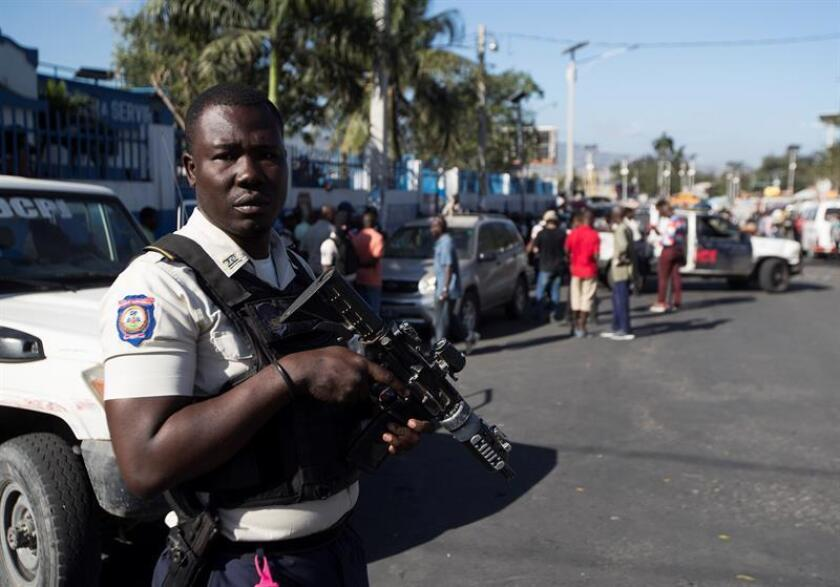 A policeman guards the area where the body of policeman Simone Jackson remains, in Port-au-Prince, Haiti, Feb. 20 2019, after being shot dead along two public transport drivers by gang members. EPA-EFE/ Orlando Barria ATTENTION EDITORS: EXPLICIT GRAPHIC CONTENT