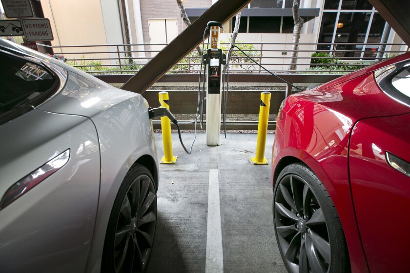 Two Tesla EVs charge in a public garage in Palo Alto.