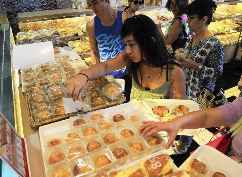 Customers look over the mooncakes at 85° C in Irvine. Mooncake season is essential to the bottom line in any Chinese or Vietnamese bakery in Southern California.