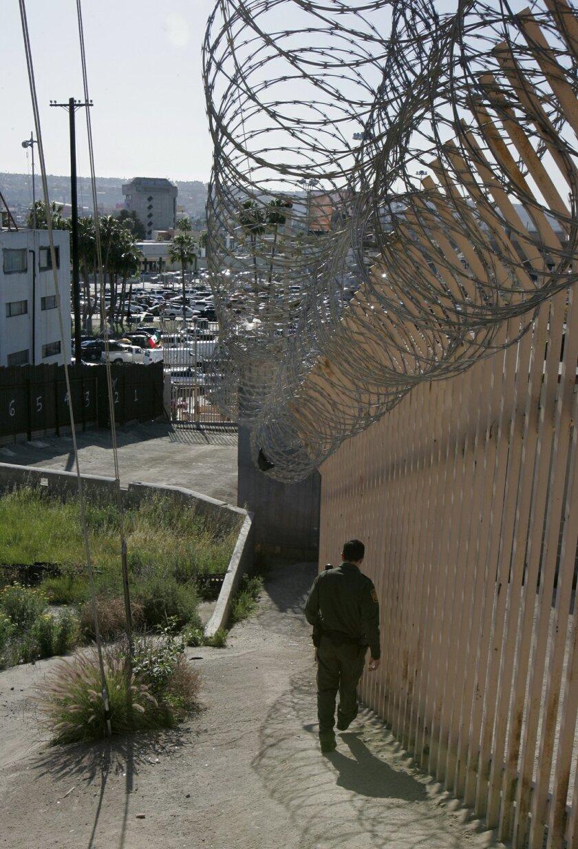 Border Patrol agent Rodolfo Zuniga walks along the secondary fence just east of the San Ysidro border crossing on March 9.  / Photo by CHARLIE NEUMAN * U-T