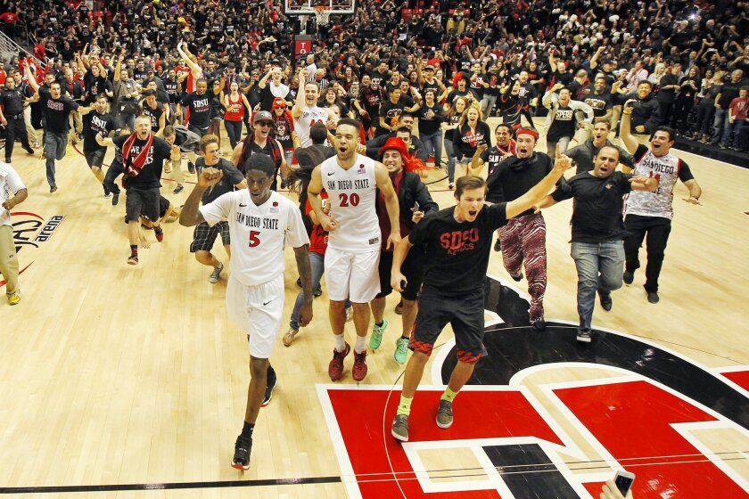 SDSU fans celebrate with Aztecs Dwayne Polee (5) and JJ O'Brien after they beat New Mexico to win the Mountain West Conference Championship on March 8, 2014.