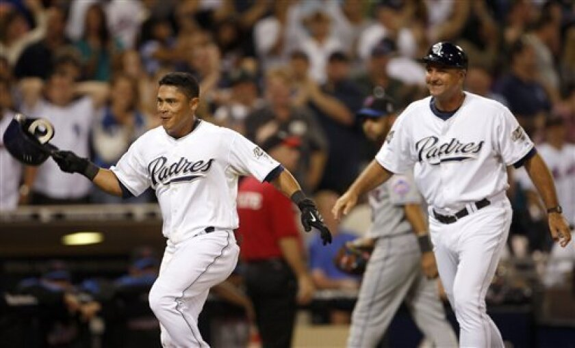 Padres' Everth Cabrera is followed by third base coach Glenn Hoffman after grand slam in ninth inning on Aug. 7, 2009.