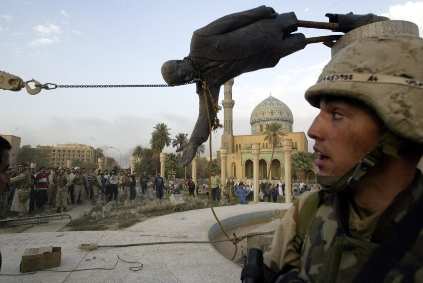 Iraqi civilians and U.S. soldiers pull down a statue of Saddam Hussein in downtown Baghdad on April 9, 2003.