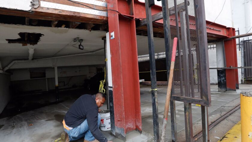 Kehl Tonga, a supervisor, adds cement to the base of a steel moment frame, to prevent water from mak
