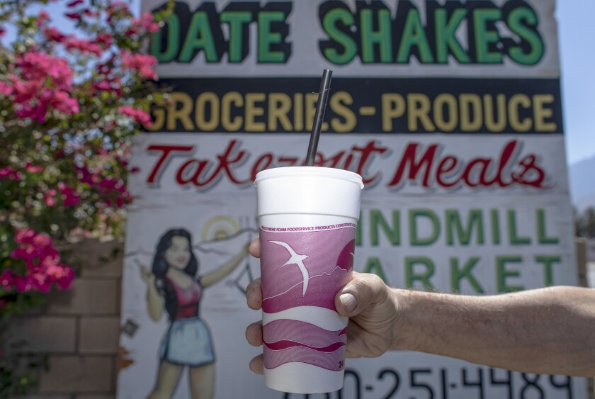 An outstretched arm holds a date milkshake in front of a sign advertising them