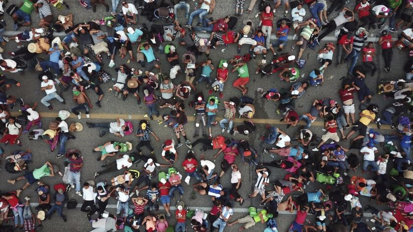 Members of a migrant caravan bound for the United States rest on a road between the Mexican states o