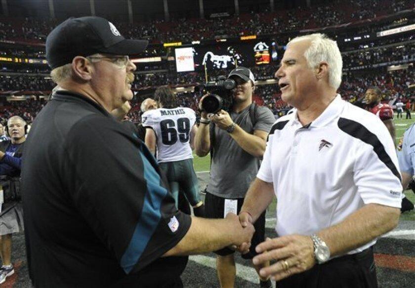 Philadelphia Eagles coach Andy Reid, left, talks with Atlanta Falcons coach Mike Smith following an NFL football game at the Georgia Dome in Atlanta on Sunday, Sept. 18, 2011. Atlanta won 35-31. (AP Photo/John Amis)