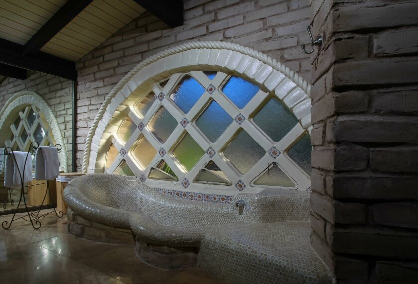 The master bathroom has a free-form tub and arched windows. Larry Weir favored unconventional styles, including circular patterns, in his adobe home designs.