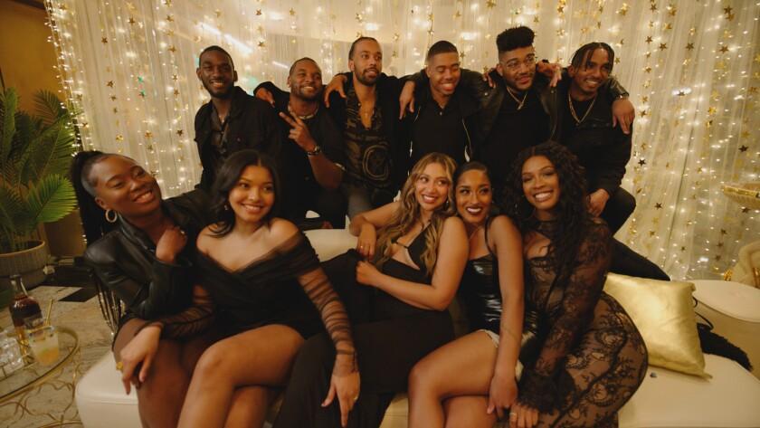 11 attractive Black men and women on and near a glitzy sofa