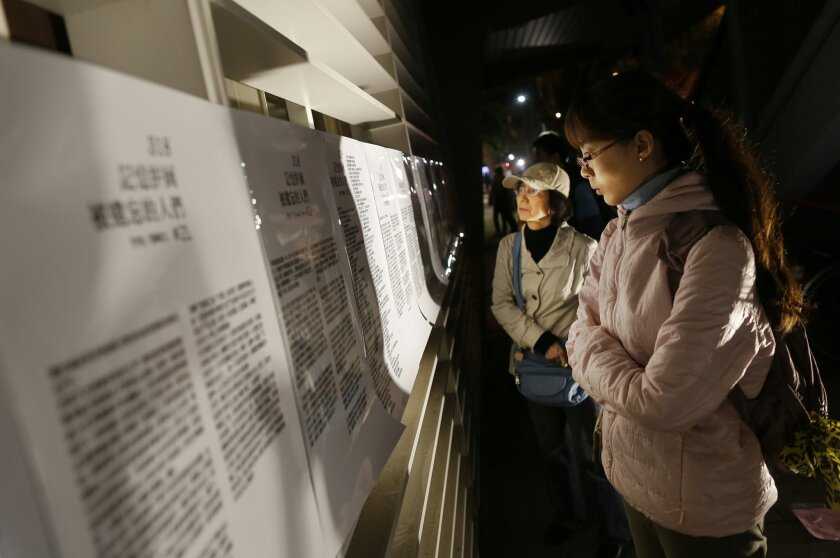 "Visitors read accounts of the 2014 student-led ""Sunflower Movement"" as protesters gather outside the parliament to mark the movement's first anniversary where student groups stormed the parliament grounds in Taipei, Taiwan, Sunday, March 22, 2015. About 300 university students gathered outside Taiw"