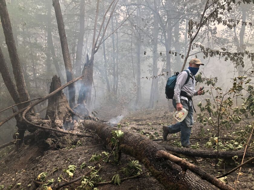 Mike Walz, 65, who fled wildfires in Mehama, Ore., carries a jug of water to douse small fires in his relatives' yard.
