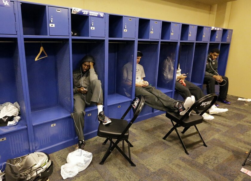 Kentucky players sit in the lockers after the NCAA Final Four tournament college basketball semifinal game against Wisconsin Saturday, April 4, 2015, in Indianapolis. Wisconsin won 71-64. (AP Photo/David J. Phillip)