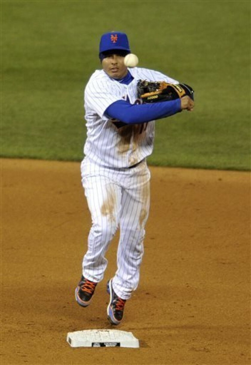 New York Mets shortstop Ruben Tejada overthrows to first base allowing two runs to score for the Colorado Rockies during the eighth inning in the second baseball game of a doubleheader Tuesday, April 16, 2013, in Denver. The Rockies beat the Mets 9-8 in 10 innings. (AP Photo/Jack Dempsey)