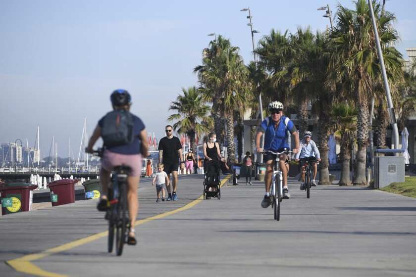 People walk and cycle at St. Kilda Beach in Melbourne, Australia
