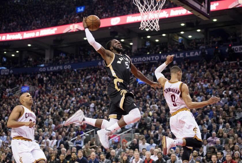 Toronto Raptors' DeMarre Carroll, center, goes for a dunk between Cleveland Cavaliers' Richard Jefferson, left, and Jared Cunningham during the first half of an NBA basketball game Wednesday, Nov. 25, 2015, in Toronto. (Darren Calabrase/The Canadian Press via AP)