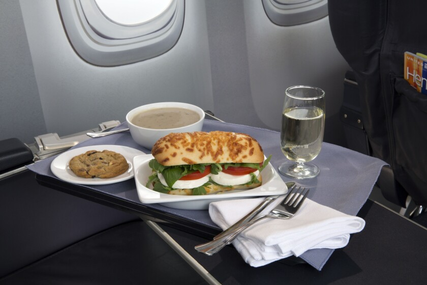 A caprese on Asiago baguette sandwich is one of a variety of United Airline's new first-class food options. Still, overall food spending by airlines per passenger continues to drop.