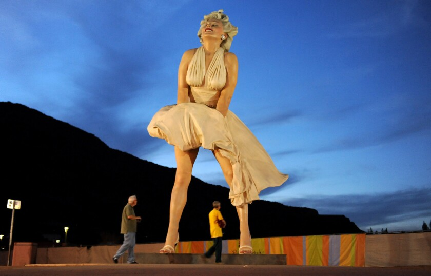 A couple walks past a 26-foot statue of Marilyn Monroe in Palm Springs.