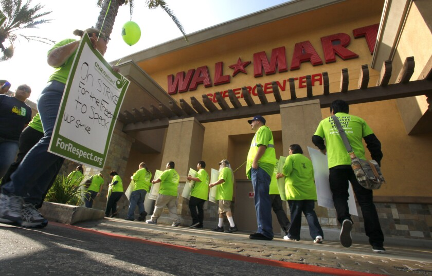 Workers protest wages and working conditions at the Pico Rivera Wal-Mart in 2012. The company is reopening the store, which has been closed for five months.