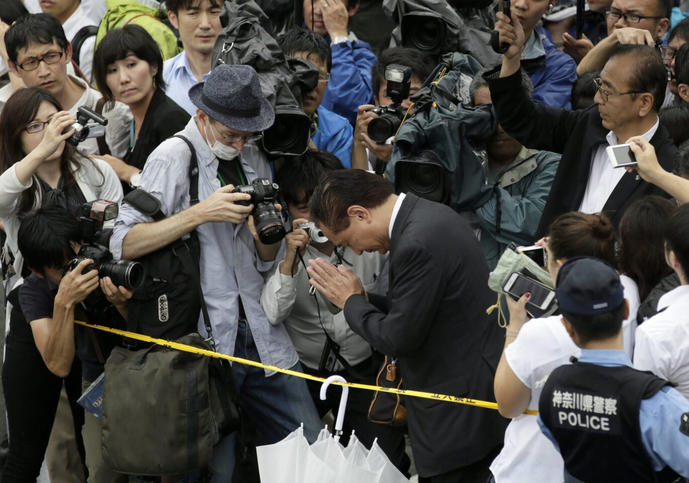 Journalists surround Kanazawa Prefecture Gov. Yuji Kuroiwa as he offers a prayer for victims killed at a residential-care facility for disabled people in Sagamihara, near Tokyo.