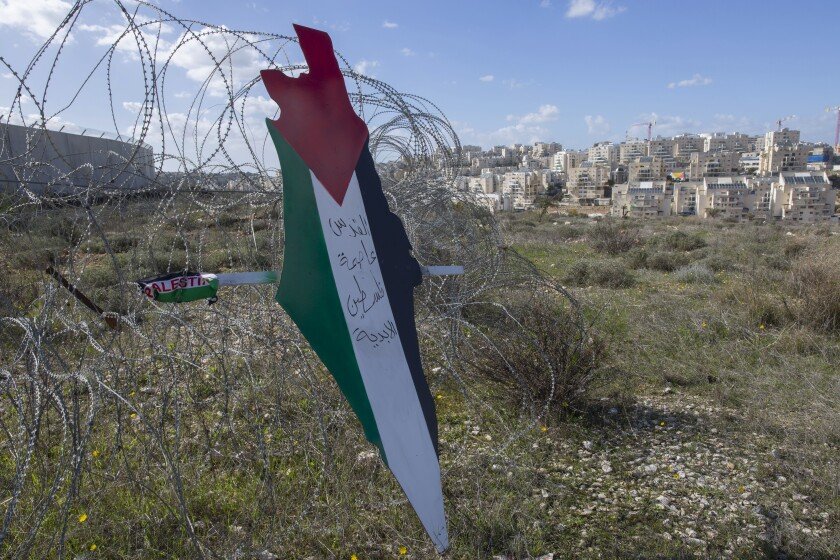 A placard shaped like a map of Israel and painted with the colors of the Palestinian flag and Arabic script.